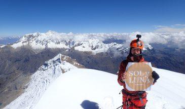 A climber on the summit of Tocllaraju